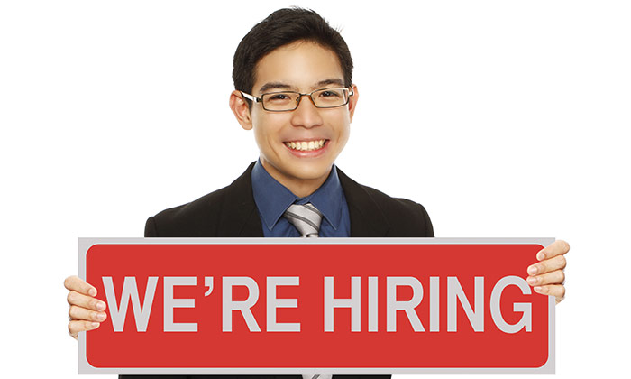We are hiring sign held by Asian businessman
