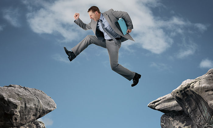 businessman jumping over skill gap