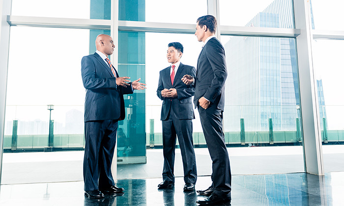 Three businesspeople standing in office lobby