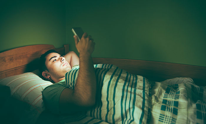 Employee sleepless in bed, checking office email