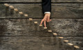 Businessman walking his fingers up steps