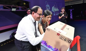 S Iswaran (left) and Euleen Goh (right), Chairman, SATS signing a parcel at the official opening of SATS eCommerce AirHub