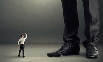 22087666 - angry businessman looking up and showing fist to his big boss
