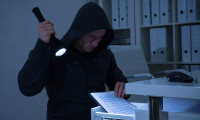 50244300 - robber with flashlight searching for documents in drawer at office