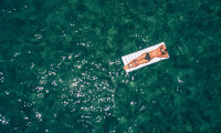 Woman floating on airbed in the sea, hr