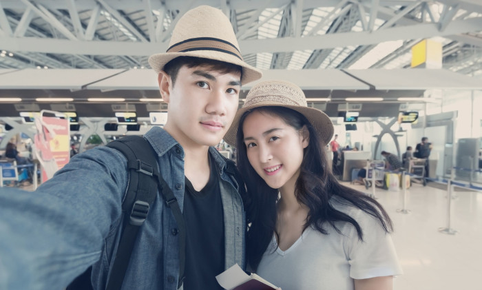 46080042 - asian couple tourist taking a selfie in airport before journey