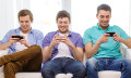 male friends playing smartphones - 123RF
