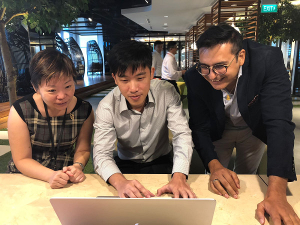 Foo Cher Fong (middle), a data scientist who joined DBS through last year's Hack2Hire programme, working with DBS colleagues.