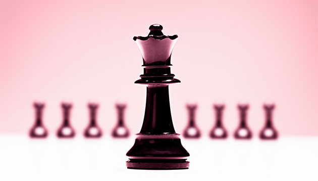 Chess queen in front of pawns - iStock